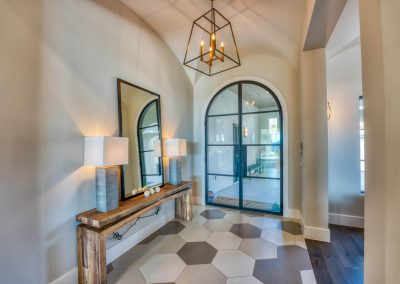 Zbranek-and-Holt-Custom-Homes-Cantera-Iron-Front-Door-Entry-Tile-Floor-Contemporary-Lighting