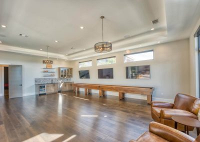 Zbranek-and-Holt-Custom-Homes-Game-Room-Shuffle-Board-Bar-TV-wall-Wood-Floor